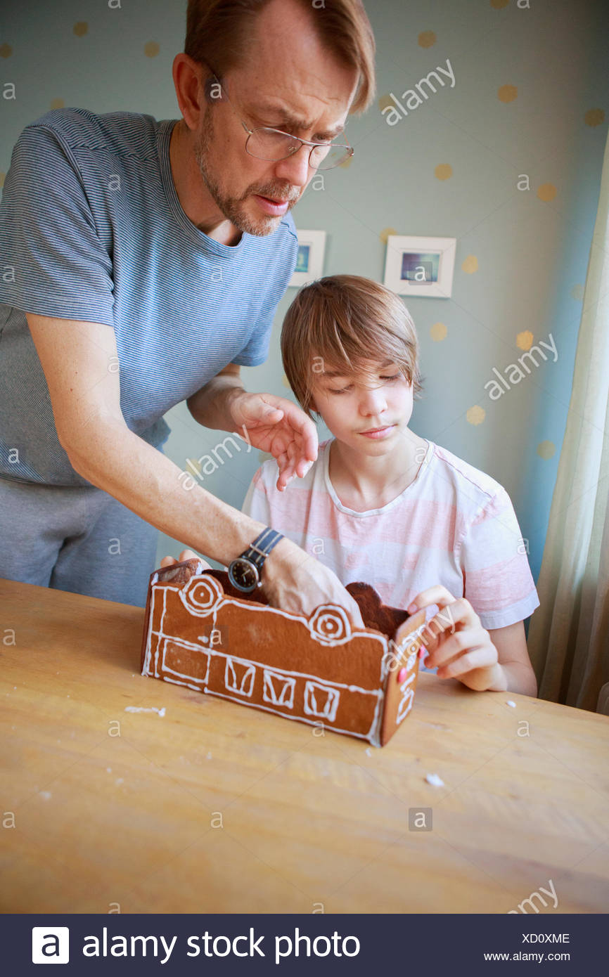 Sweden, Father and son (14-15) making cookie bus - Stock Image