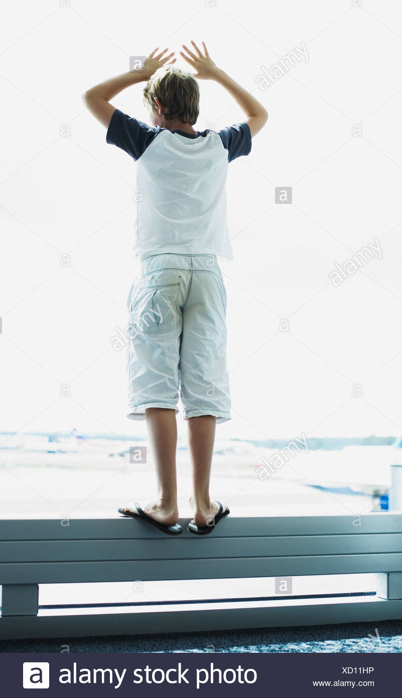 A boy looking out a window at an airport - Stock Image