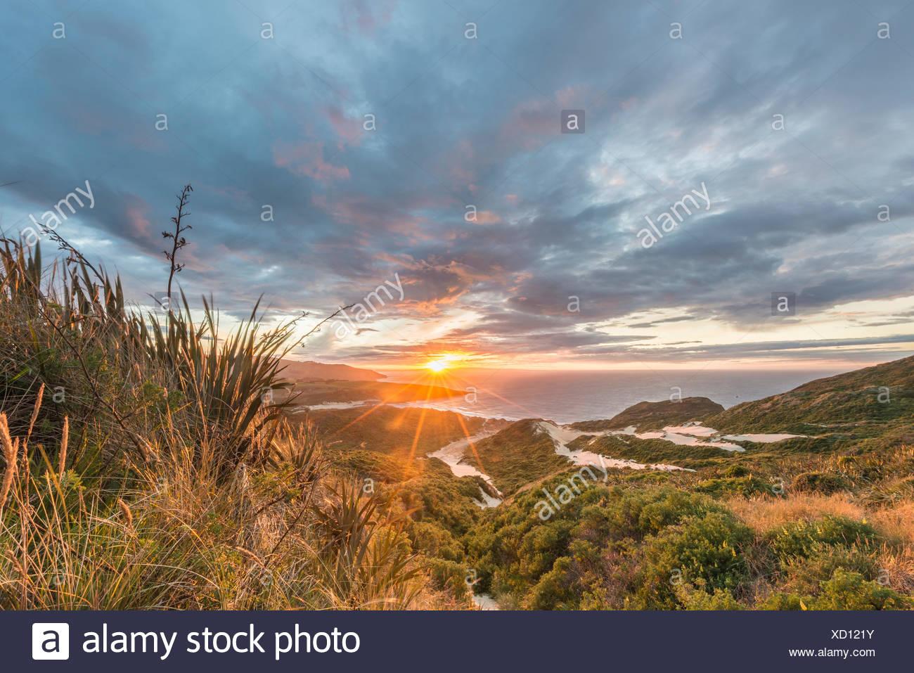 Sunset over the sea, sand dunes, Sandfly Bay, Dunedin, Otago, Otago Peninsula, Southland, New Zealand - Stock Image