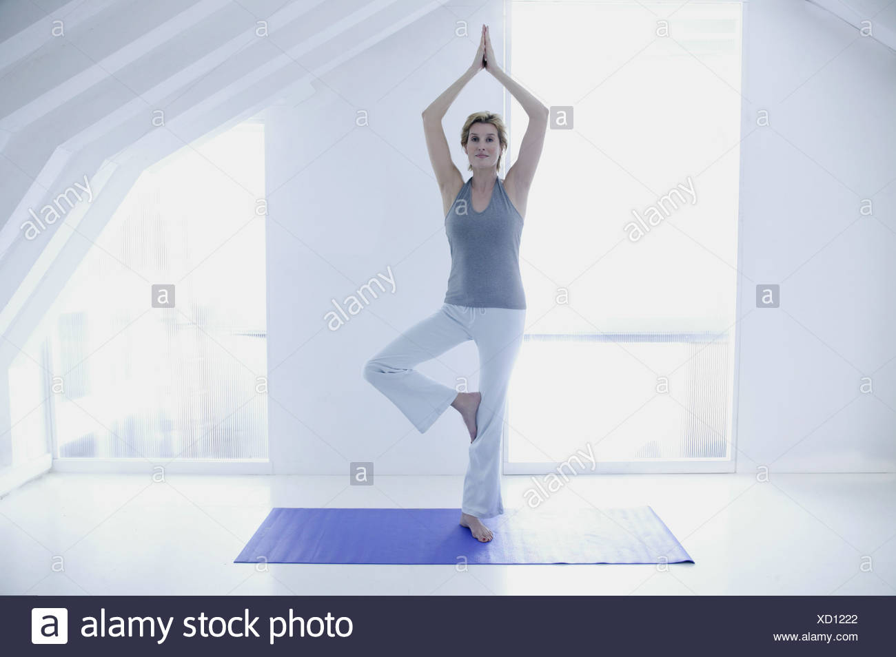 A woman in her forties doing yoga - Stock Image