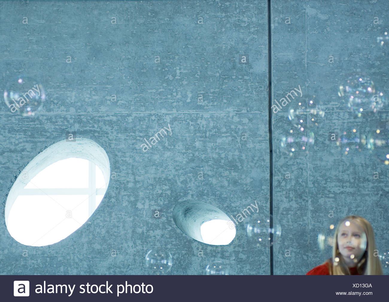 Girl watching bubbles floating in the air - Stock Image