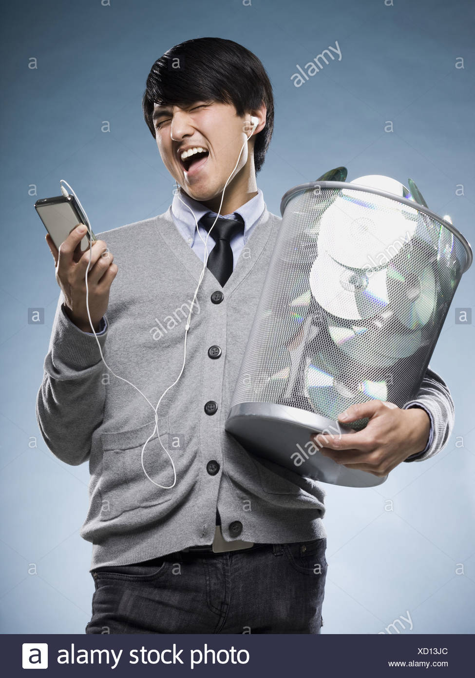 man with a trash can full of cd's and holding an iPod - Stock Image
