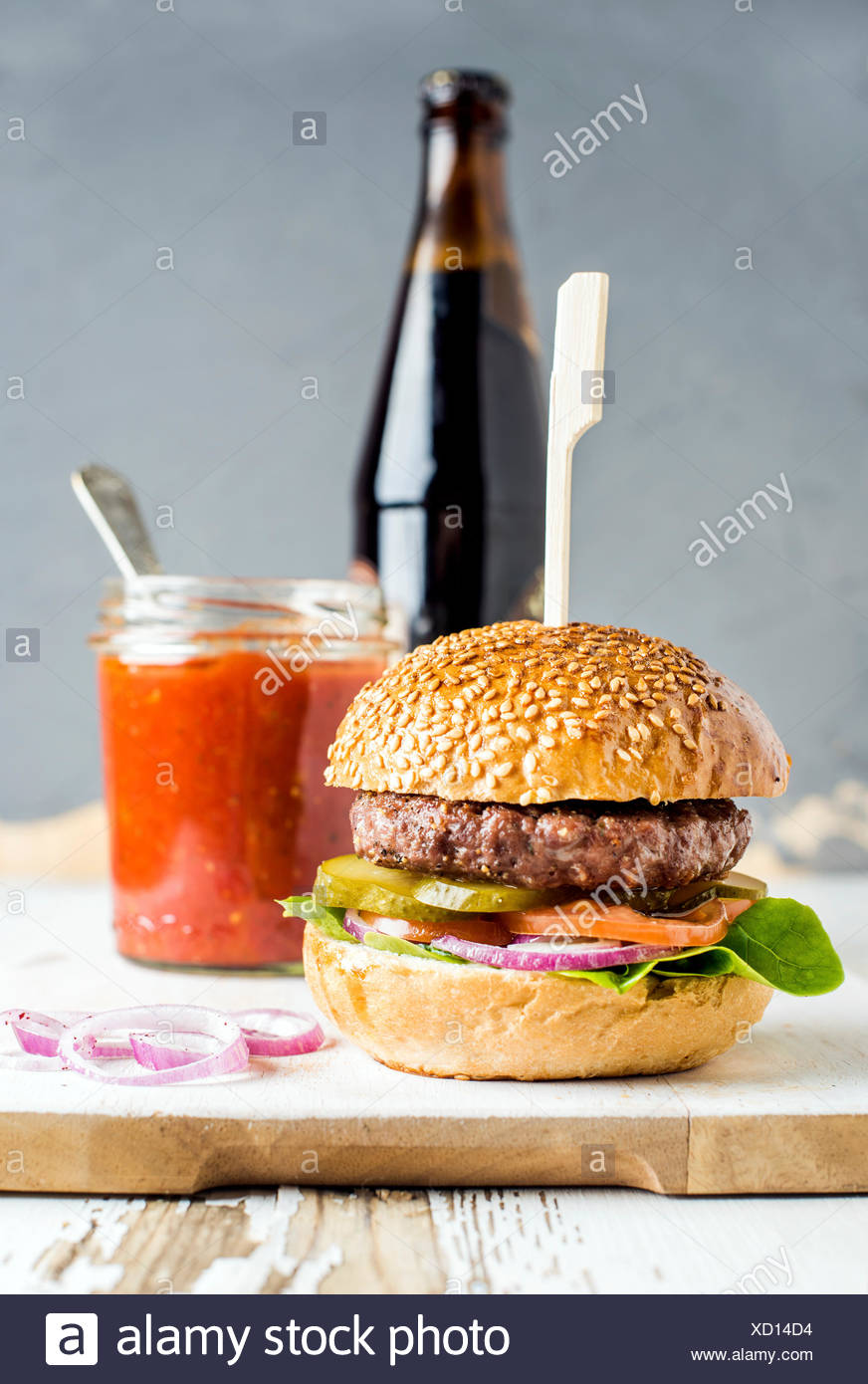 Fresh homemade burger on white wooden serving board with onion rings, salsa sauce and bottle of beer over white background, sele - Stock Image