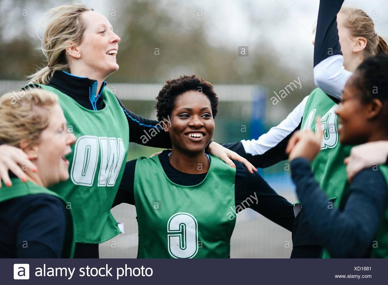 Female netball team celebrating win on netball court - Stock Image