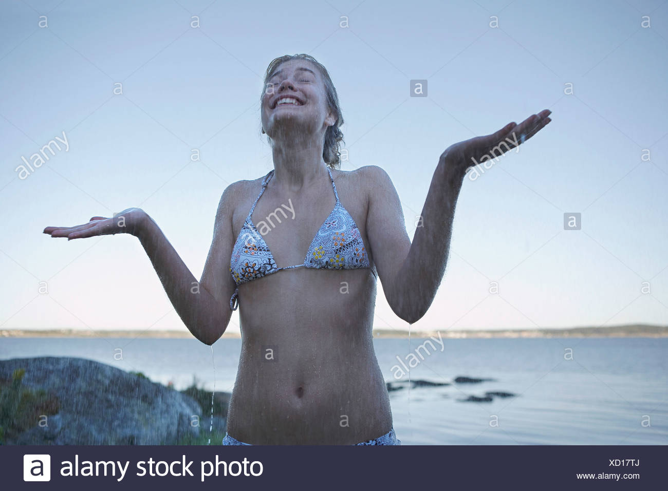 Young Woman in rain wearing bikini - Stock Image