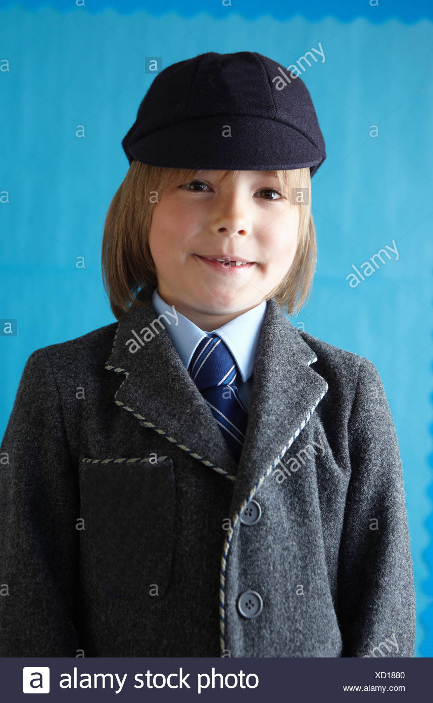 Boy in school uniform smiling at camera with a toothy grin - Stock Image