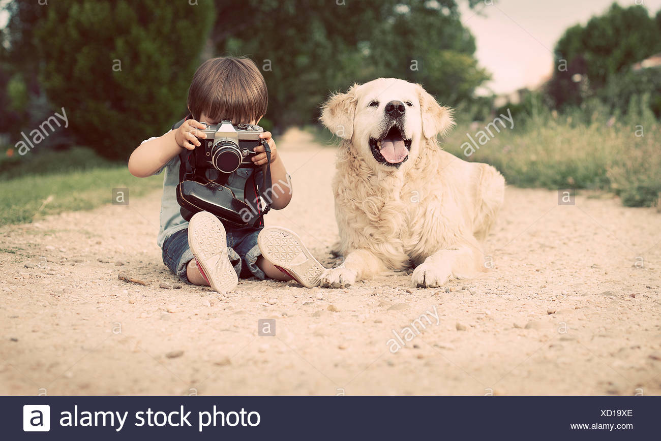 Boy with his dog sitting and photographing with old camera - Stock Image