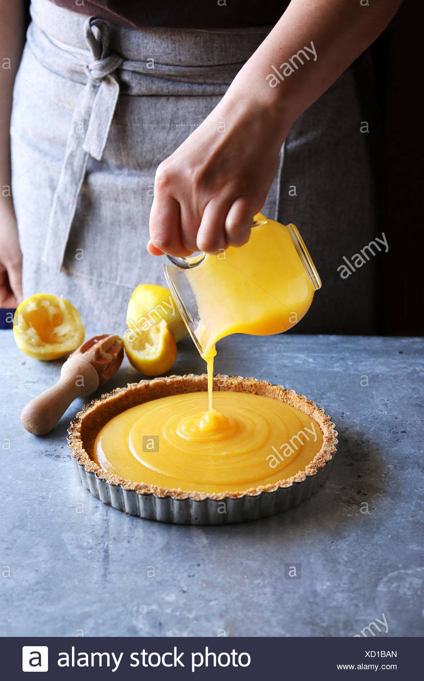 Female hand pouring lemon curd in a pastry shell. - Stock Image