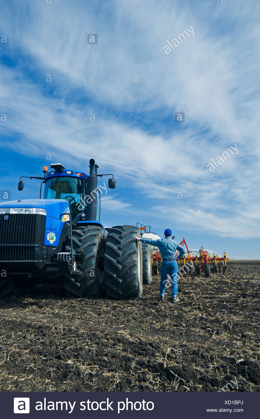 a man beside tractor and air till seeding equipment, near St. Agathe, Manitoba, Canada - Stock Image