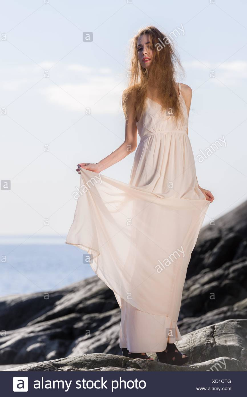 Beautiful young woman wearing white dress, scandinavian shore and sea on background. - Stock Image
