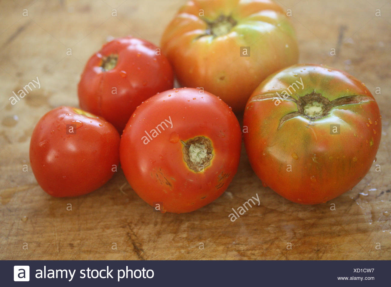 Five Heirloom Tomatoes on wooden chopping board - Stock Image