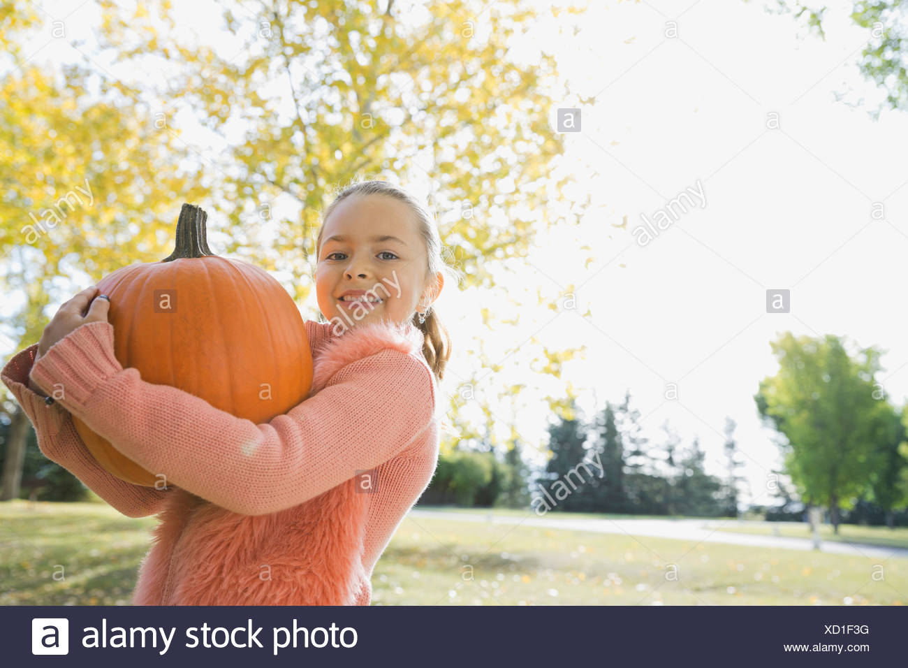 Portrait of happy girl carrying pumpkin - Stock Image