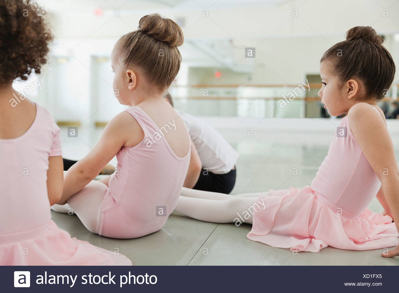 Children doing stretching exercises in ballet studio - Stock Image