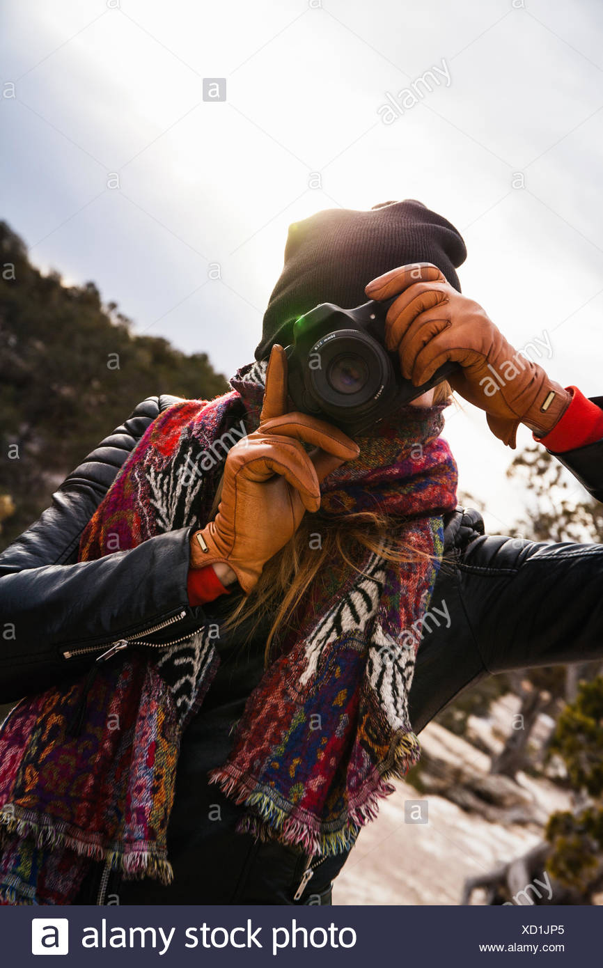 Woman photographing in front of river - Stock Image
