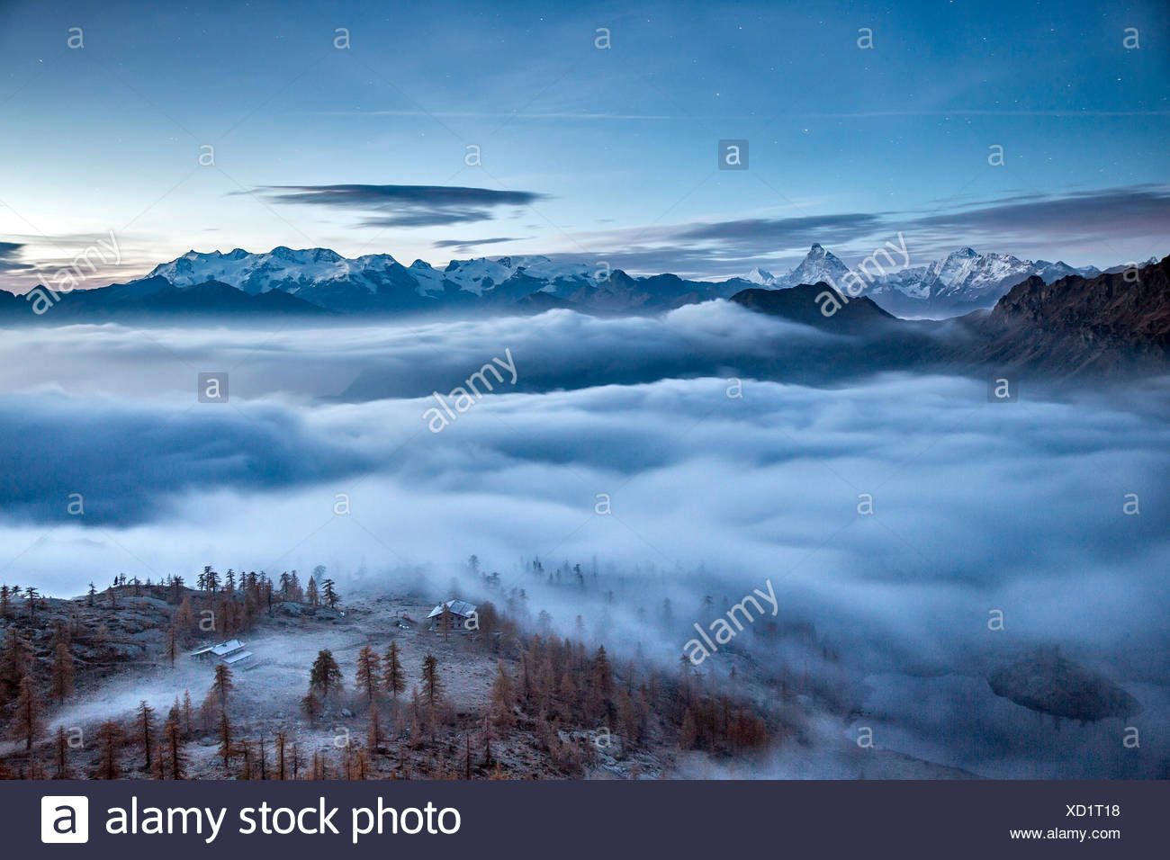 Fog covering Aosta valley at sunrise. Only the Matterhorn and the Monte Rosa emerge like islands from the sea of clouds - Mont Avic natural park, Aosta valley, Italy - Stock Image