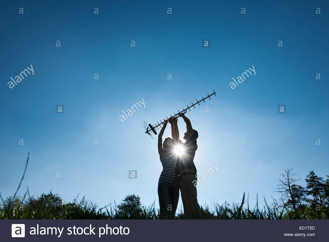 Couple holding up antenna outdoors - Stock Image