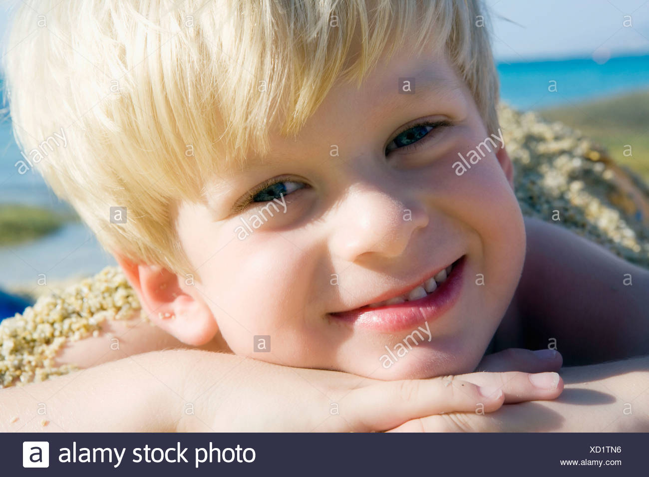 Young boy lying in the sand at the beach smiling. Stock Photo
