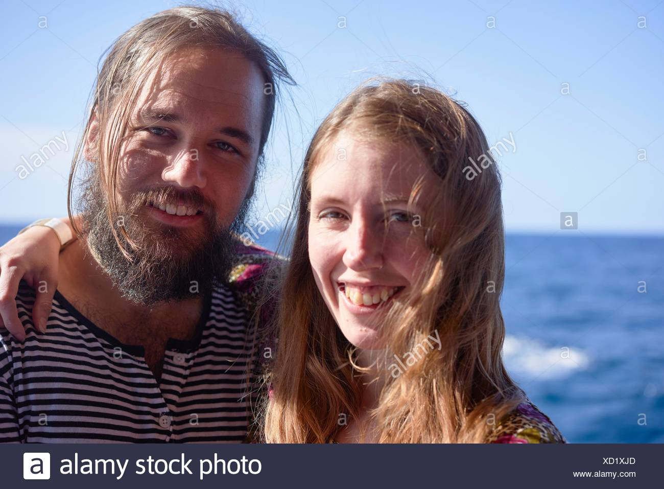 happy Scandinavian Couple next to sea during vacations in Gozo, Malta, Europe - Stock Image