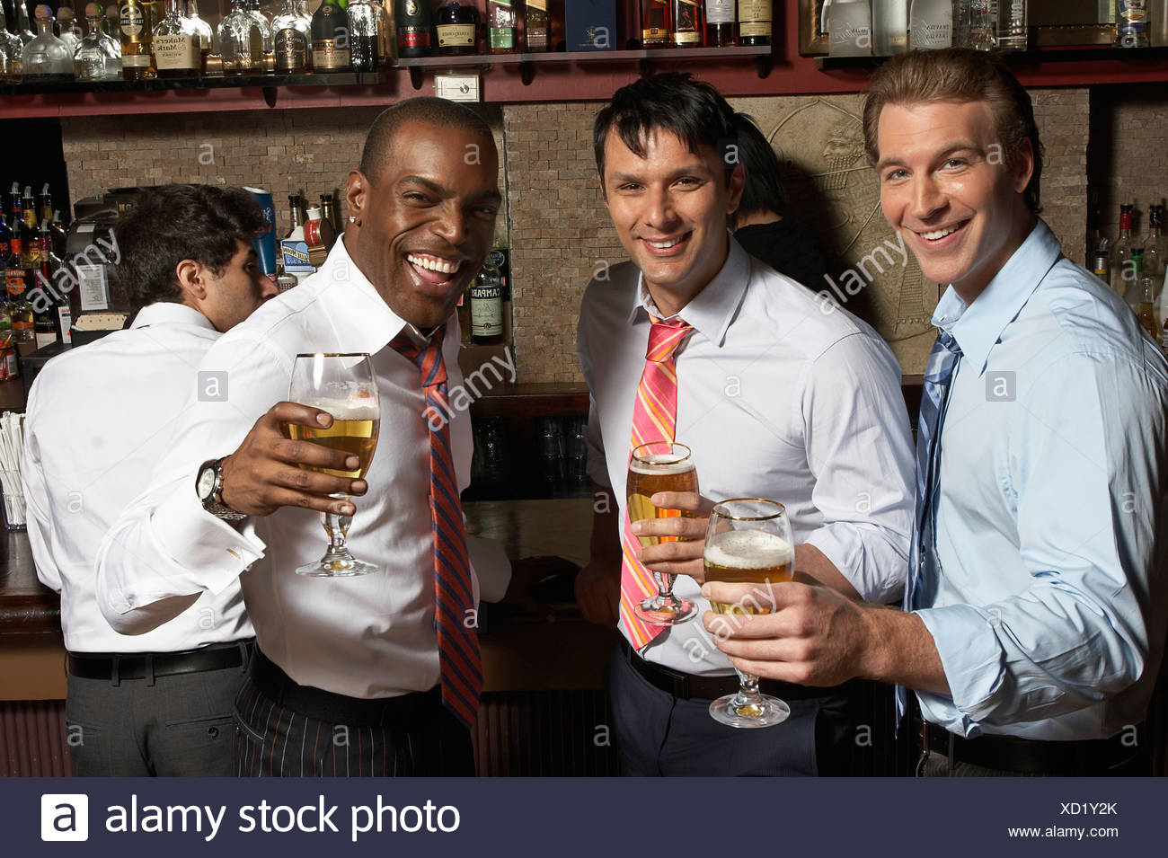 Three businessmen at bar with drinks - Stock Image