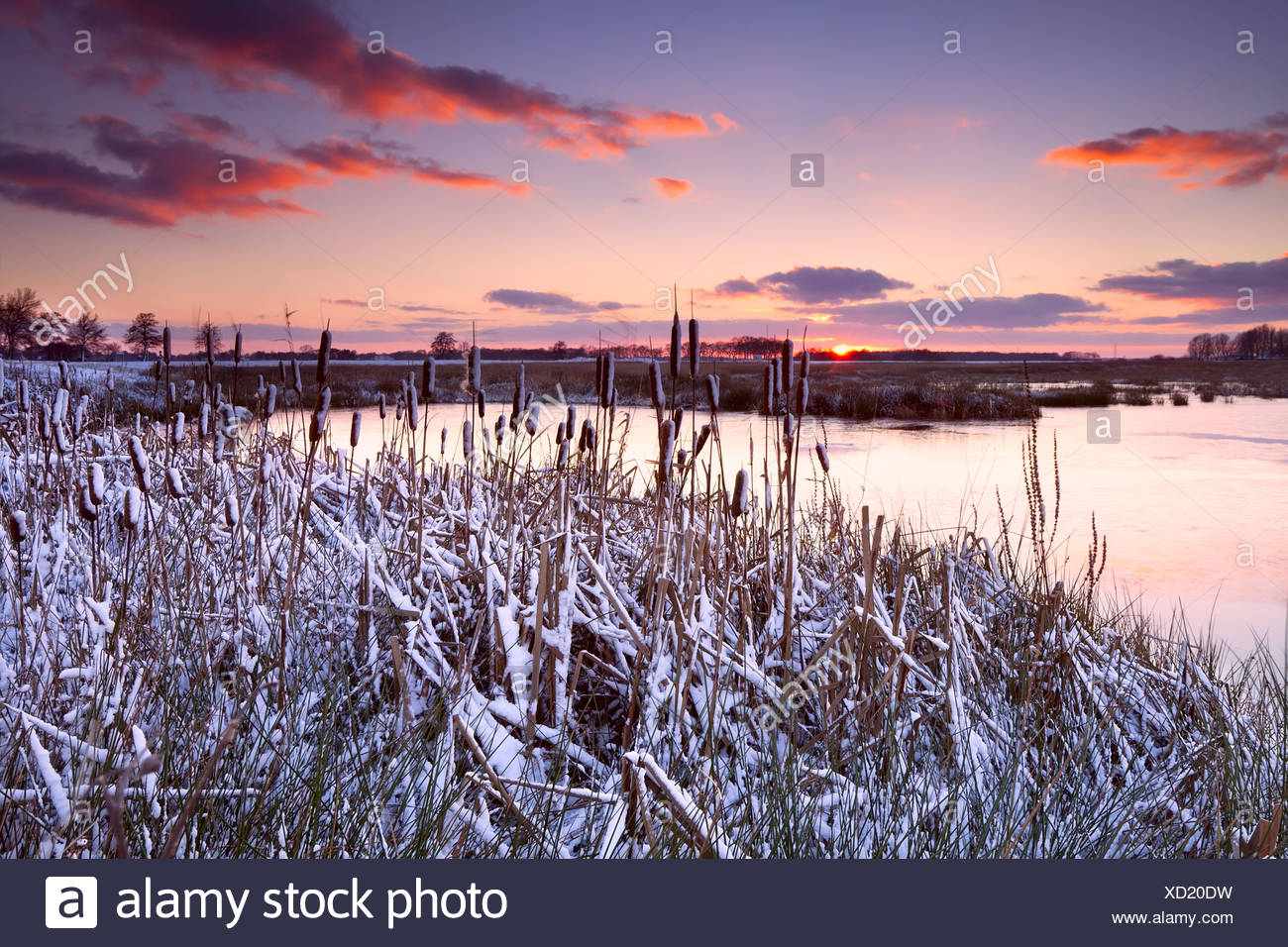dramatic sunrise over frozen lake - Stock Image
