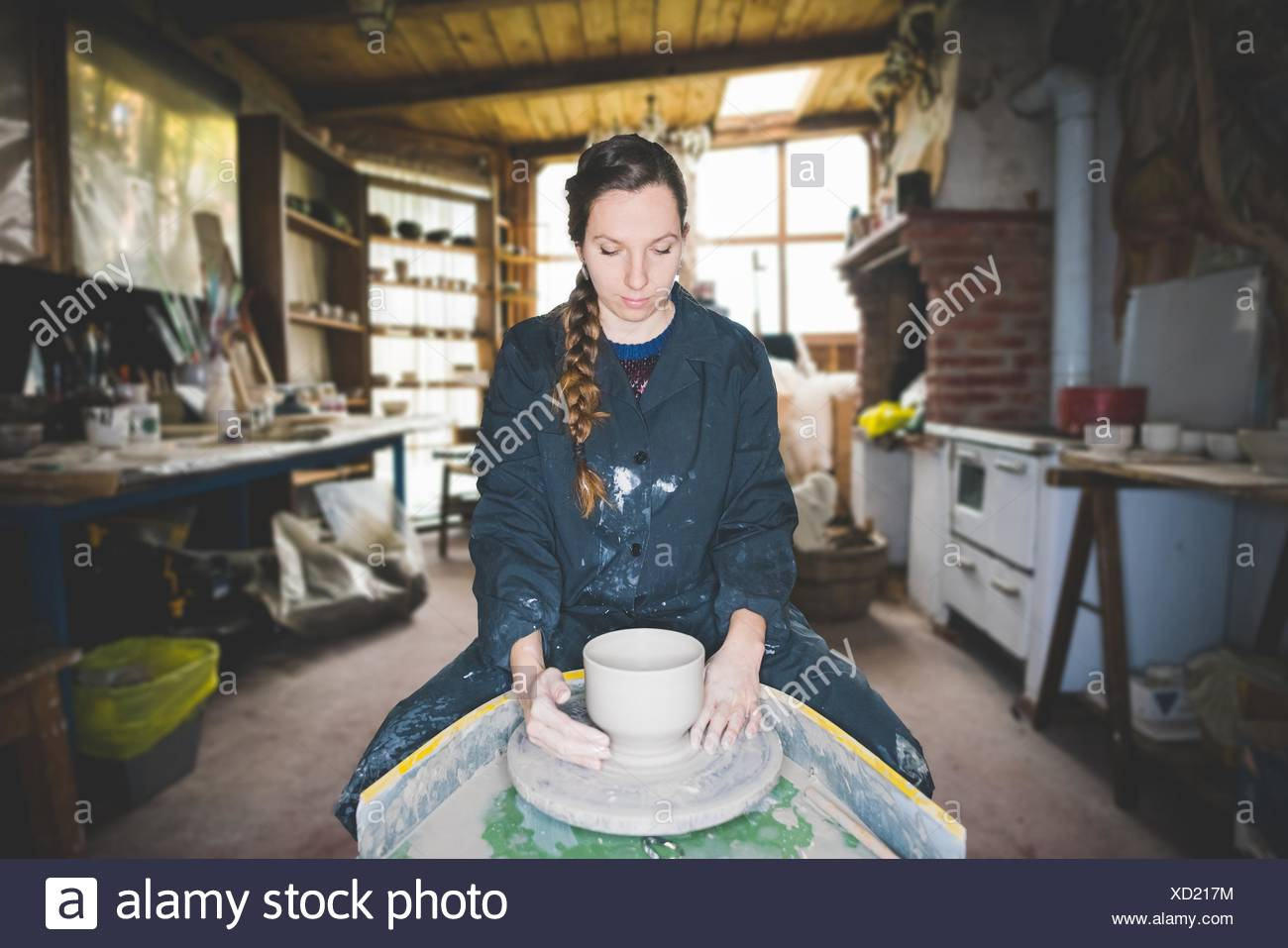 Front view of young woman in workshop sitting at pottery wheel making clay pot, looking down - Stock Image