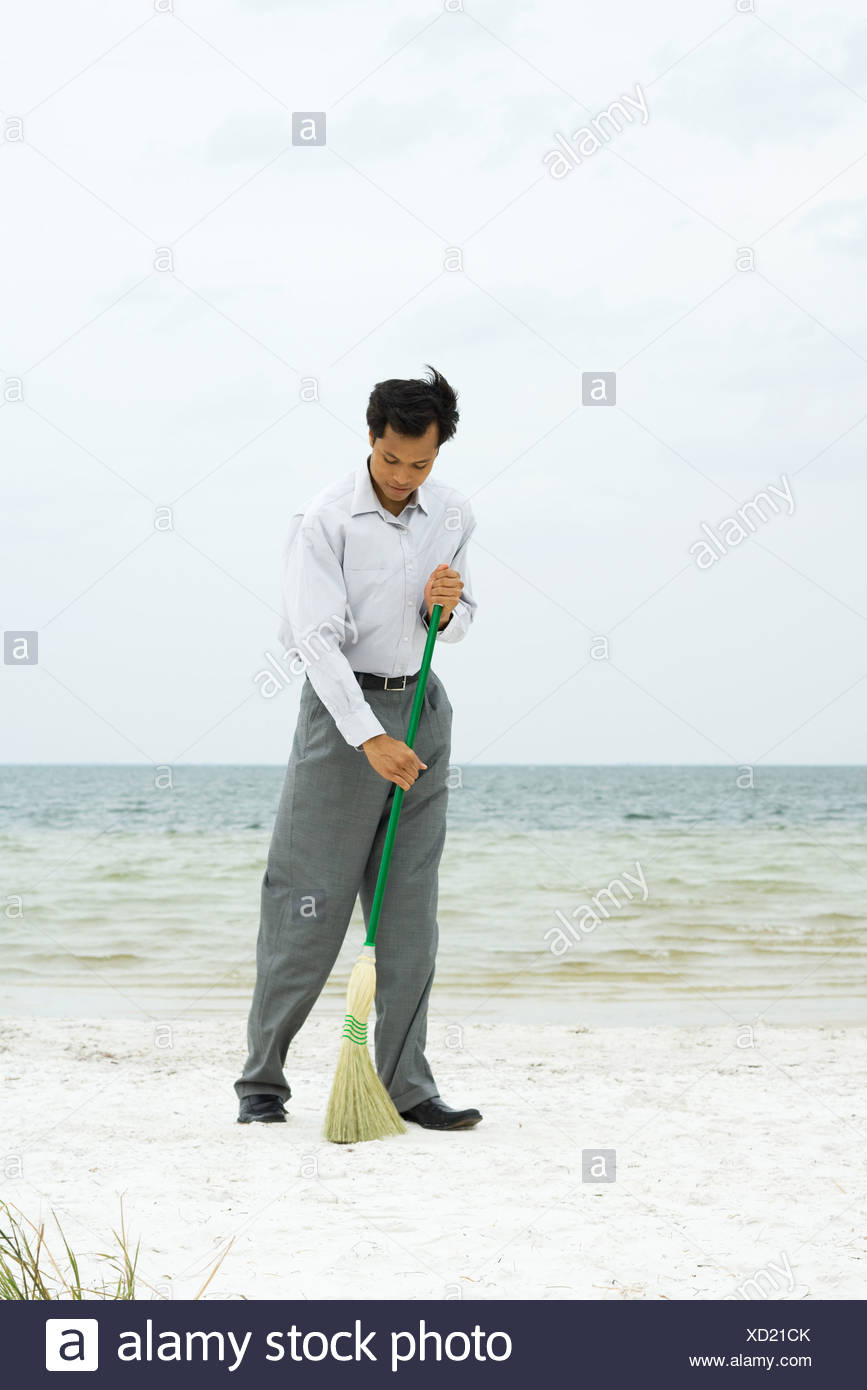 Man standing on beach sweeping with broom, full length Stock Photo