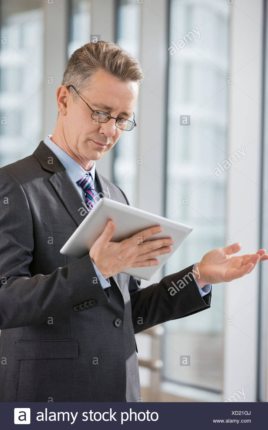 Businessman gesturing while using tablet PC in office - Stock Image
