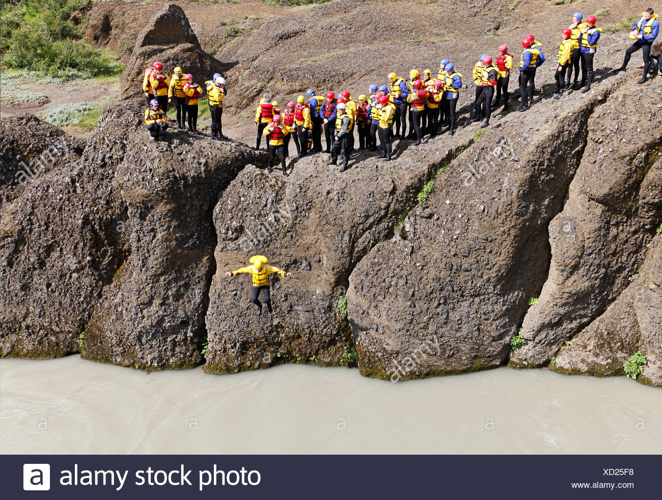 Visitors on a rafting tour having to pass a test of courage and jump into the cold water of the Hvita river before they get into - Stock Image