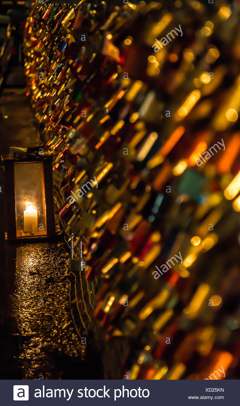Love Padlocks On Fence Against Lit Candle At Night - Stock Image