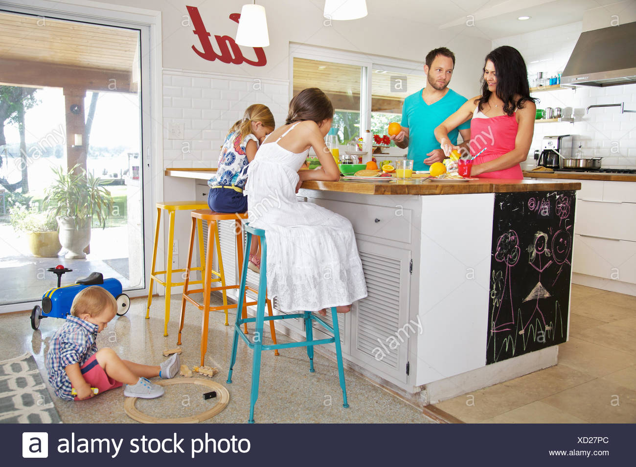 Mid adult parents and three children preparing breakfast in kitchen - Stock Image