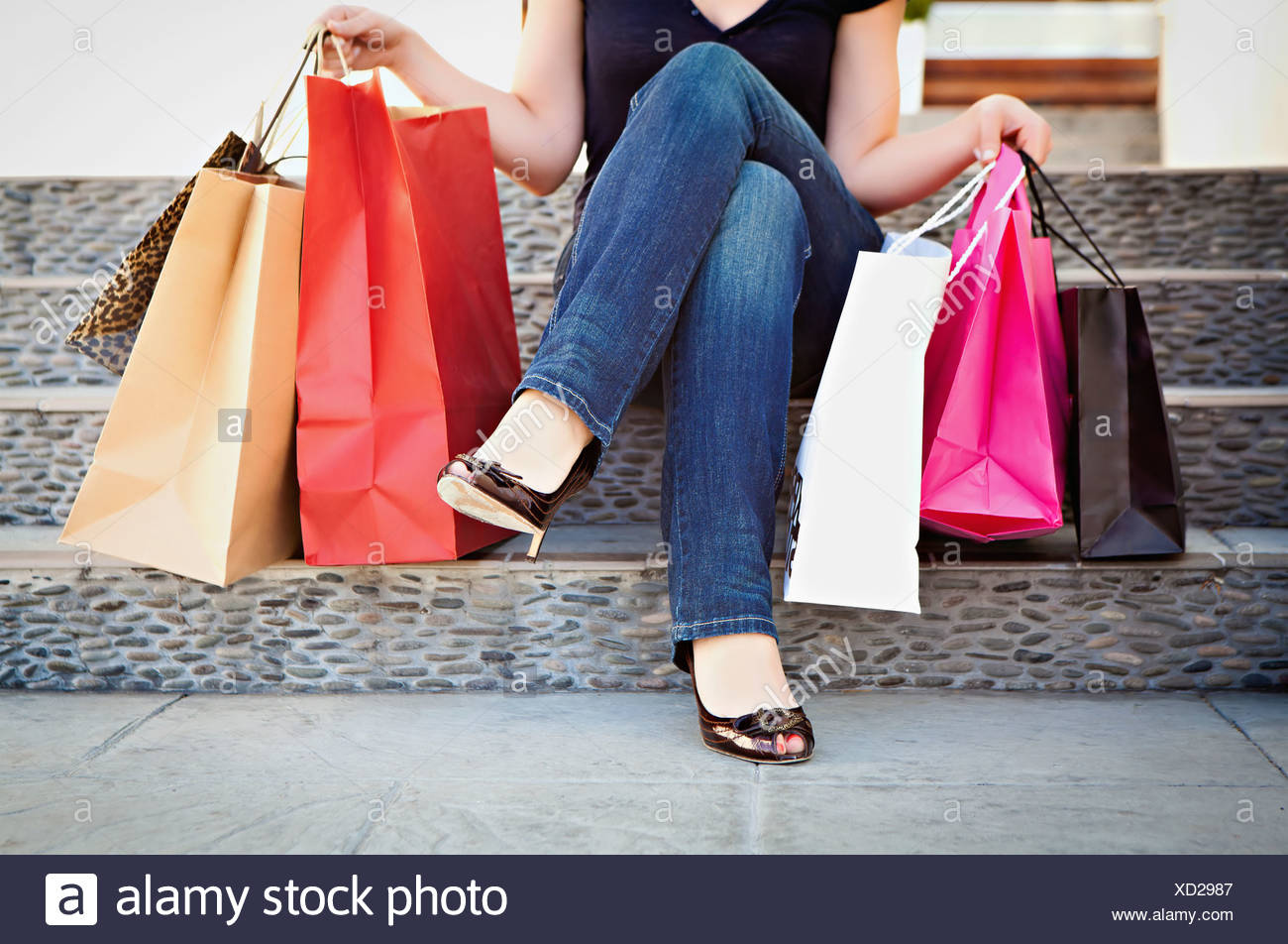 USA, California, Lawndale, Woman sitting on steps with shopping bags - Stock Image