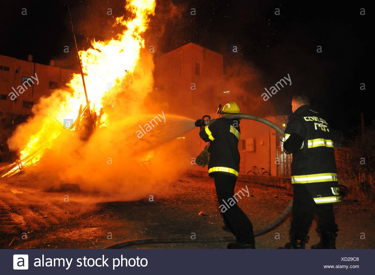 Israel, Haifa, Firefighter extinguish a large bonfire during the lag b'omer celebrations - Stock Image