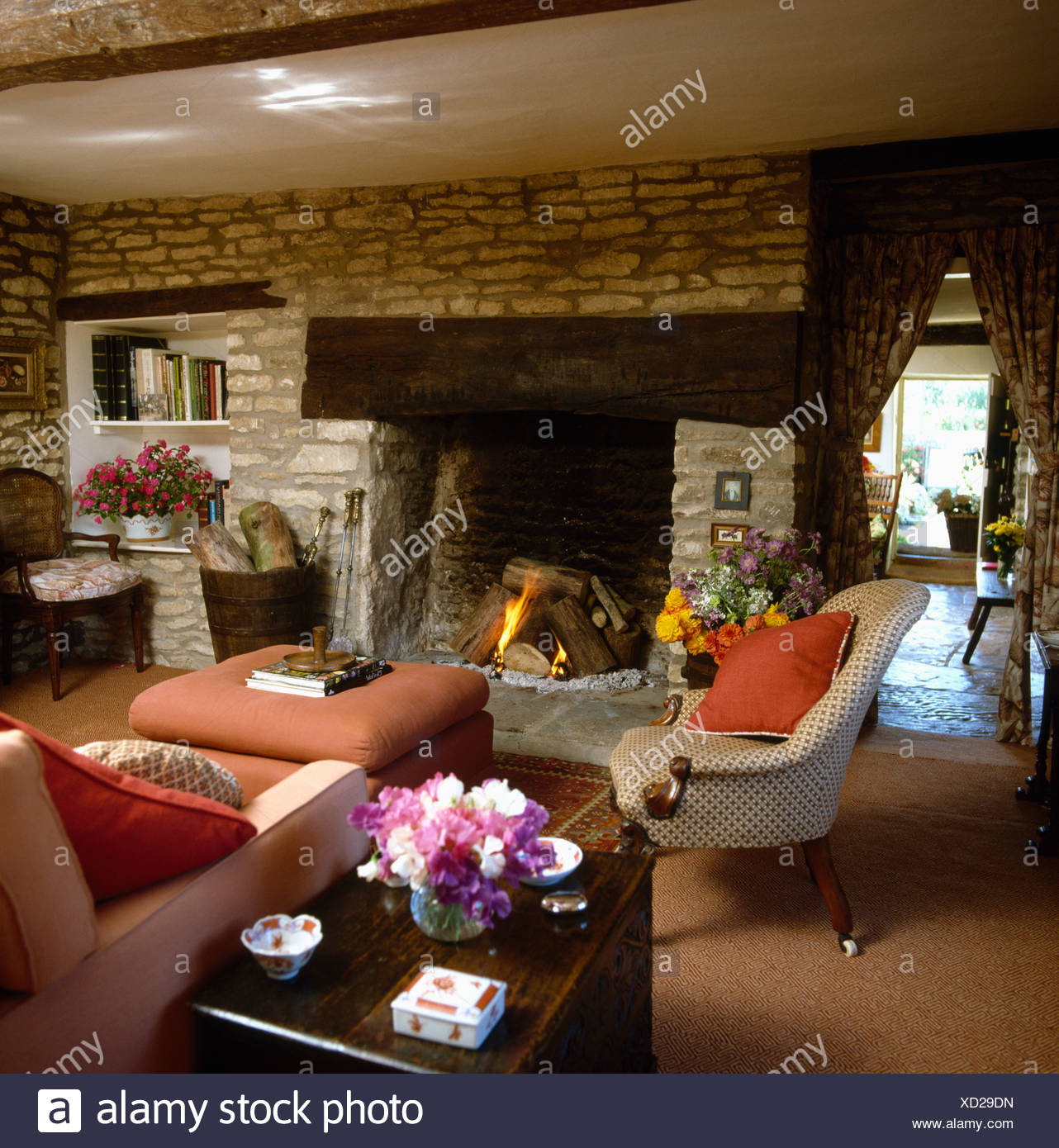 Inglenook fireplace in country cottage livingroom with stone wall and comfortable furniture - Stock Image