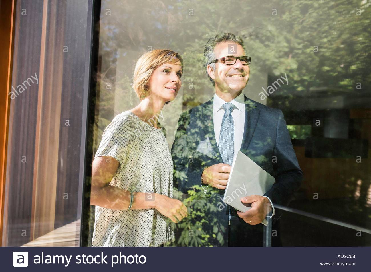 Mature woman looking through window of new house with estate agent - Stock Image