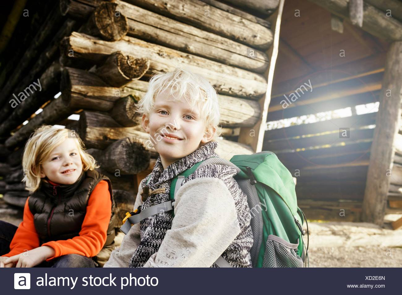 Blonde haired brother and sister sitting outside log cabin looking at camera smiling - Stock Image