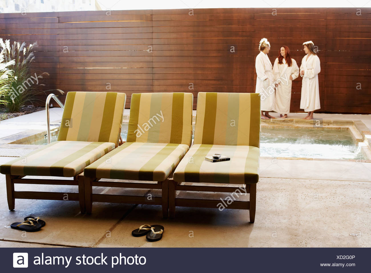 Three empty lounge chairs with three women in the background - Stock Image