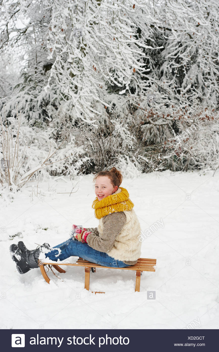 Girl sitting on wooden sled in snow - Stock Image
