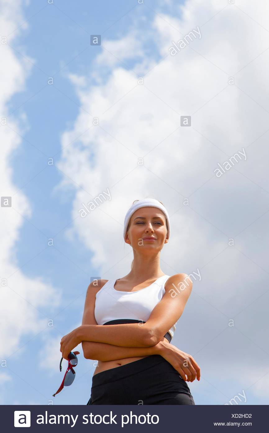 Portrait of jogger against blue skies - Stock Image