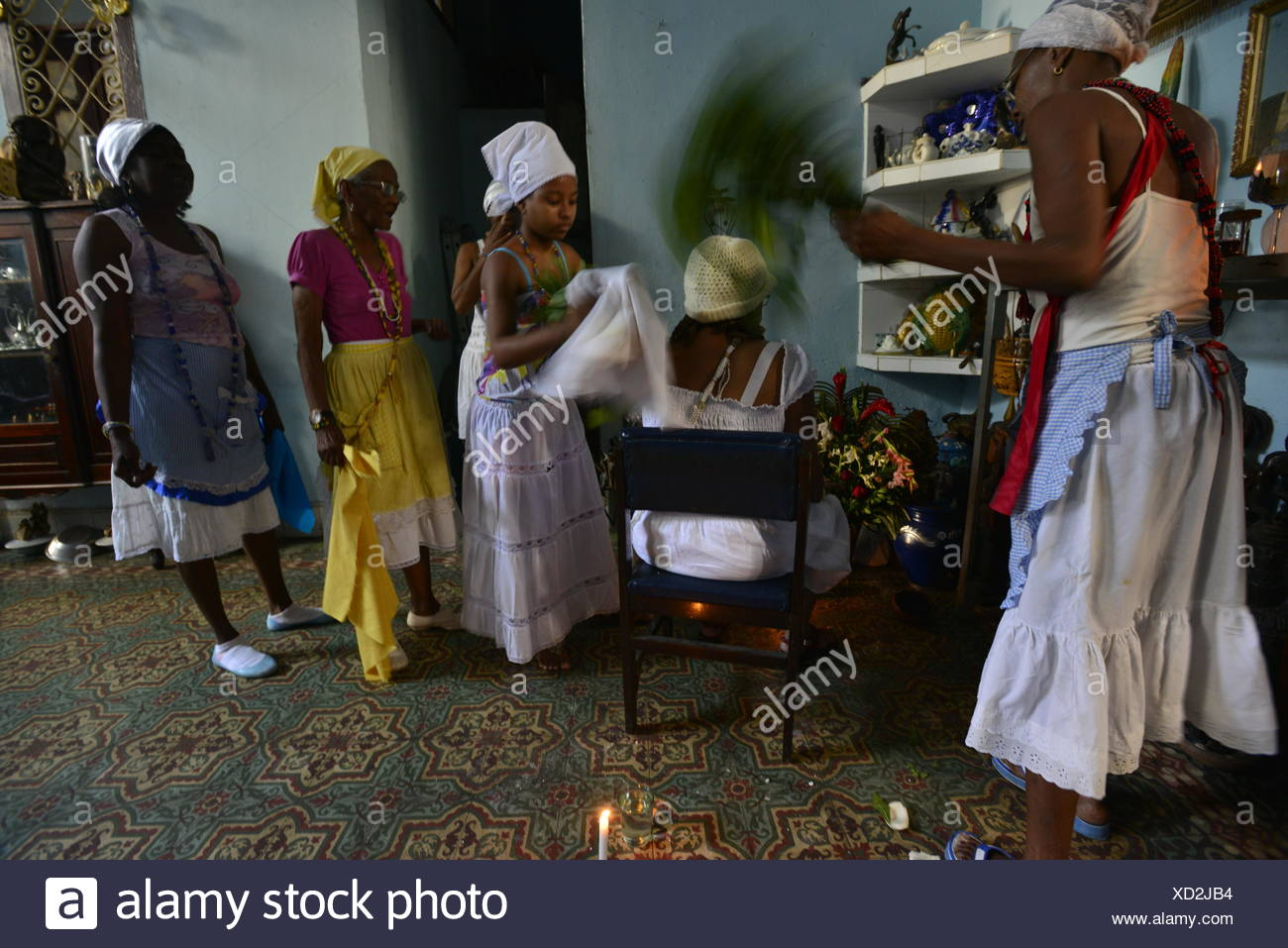 Wearing a yellow skirt, the Palero or Priestess from the Regla de Palo Monte religion performing Santeria rituals. - Stock Image
