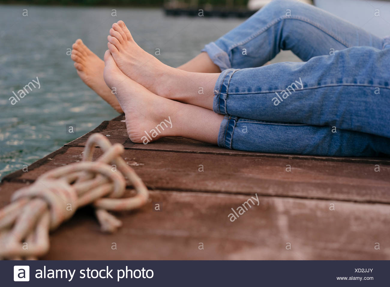 Two women relaxing on pier, focus on barefeet - Stock Image