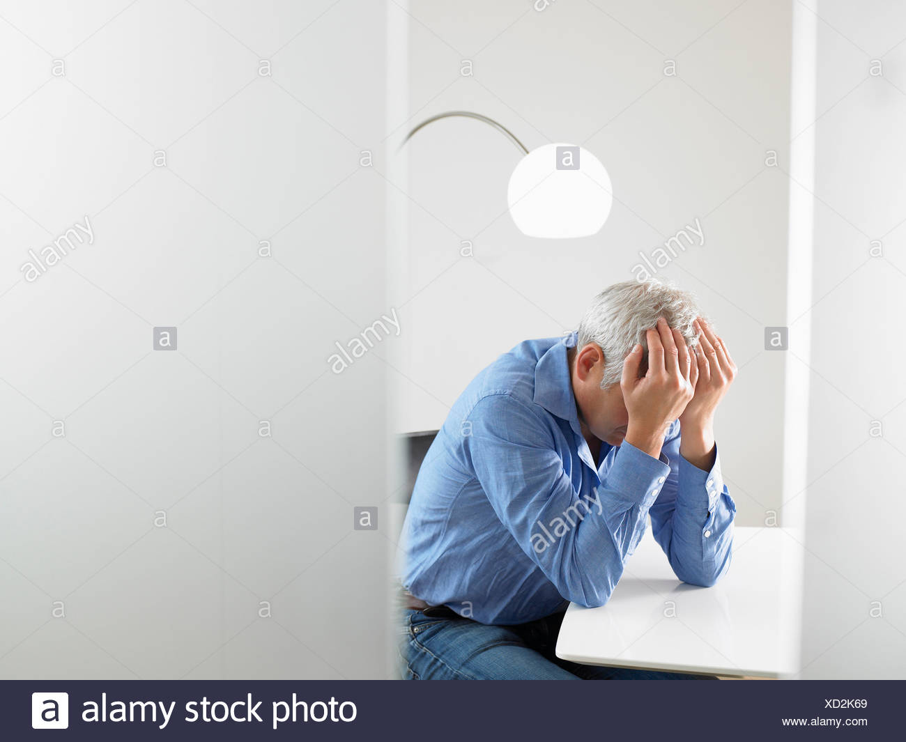 Desperate man at his desk - Stock Image