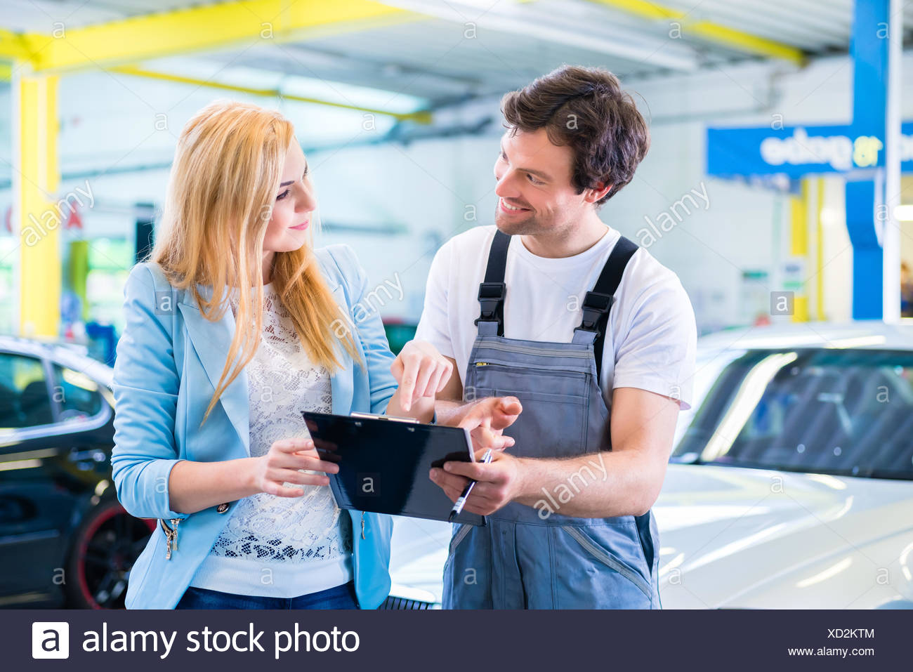 Male workshop mechanic handover car with checklist to client - Stock Image