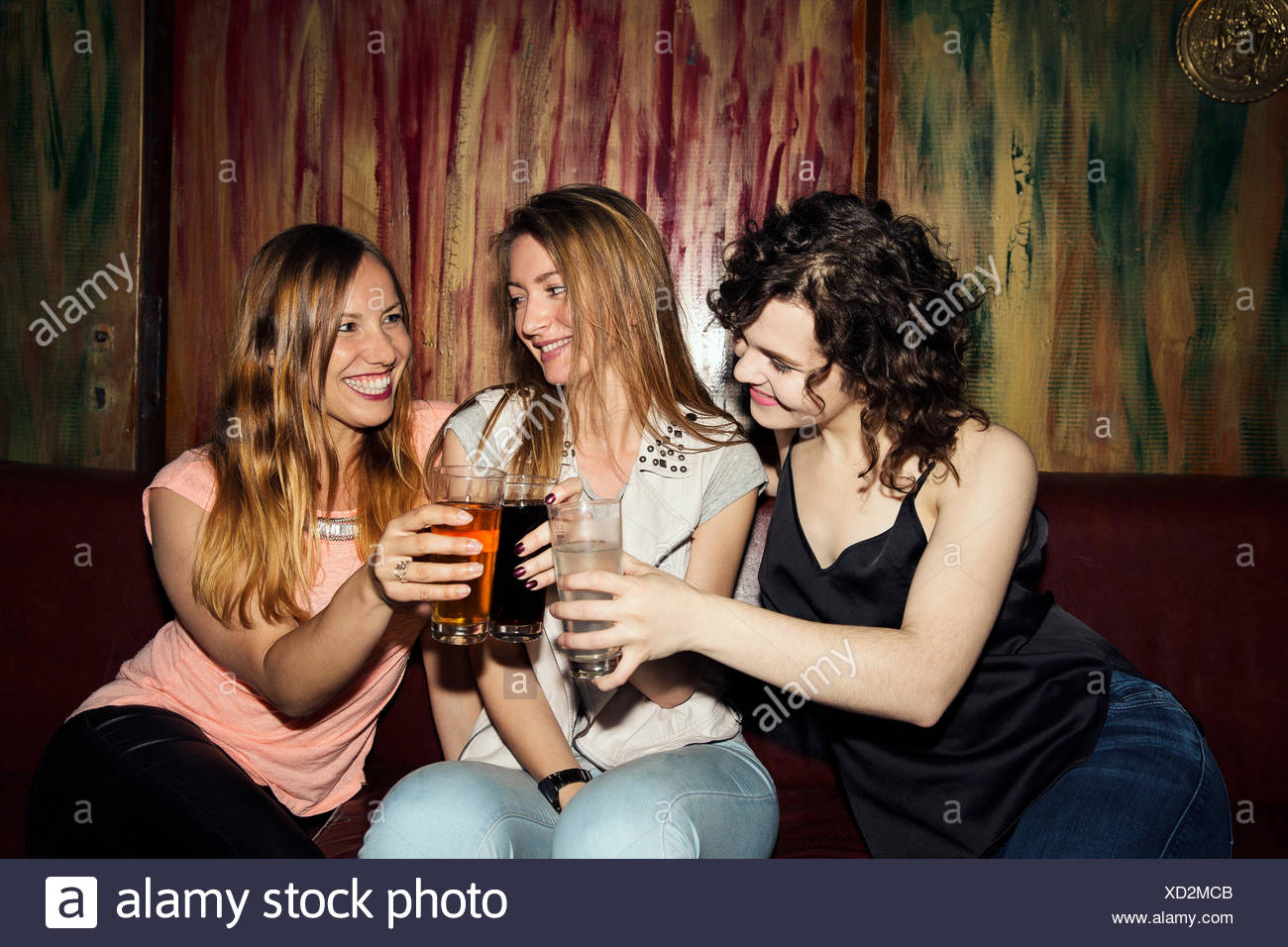 Three adult female friends raising a glass whilst sitting in bar - Stock Image
