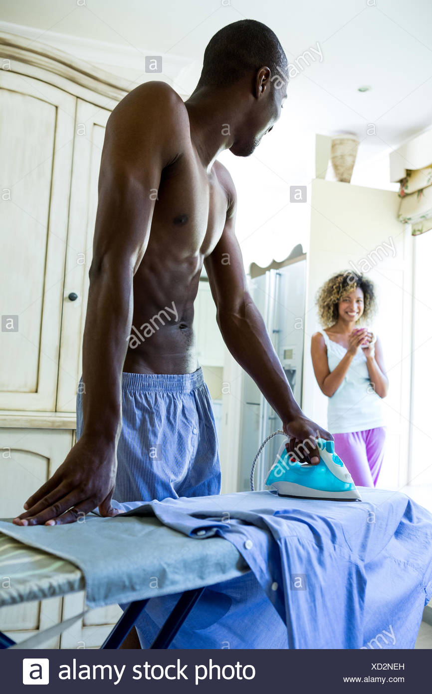 Young man ironing a shirt in kitchen - Stock Image