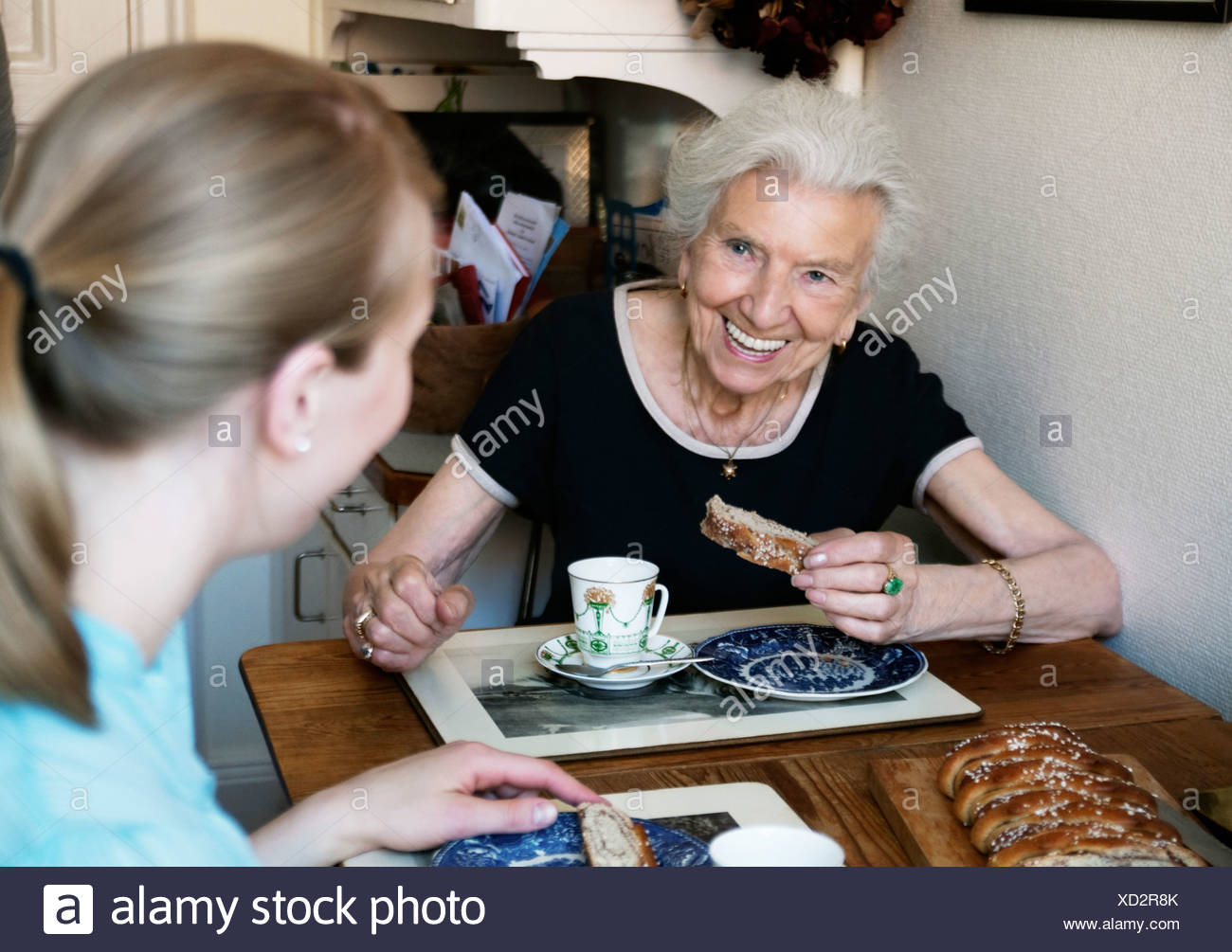 Two women sitting and eating buns - Stock Image