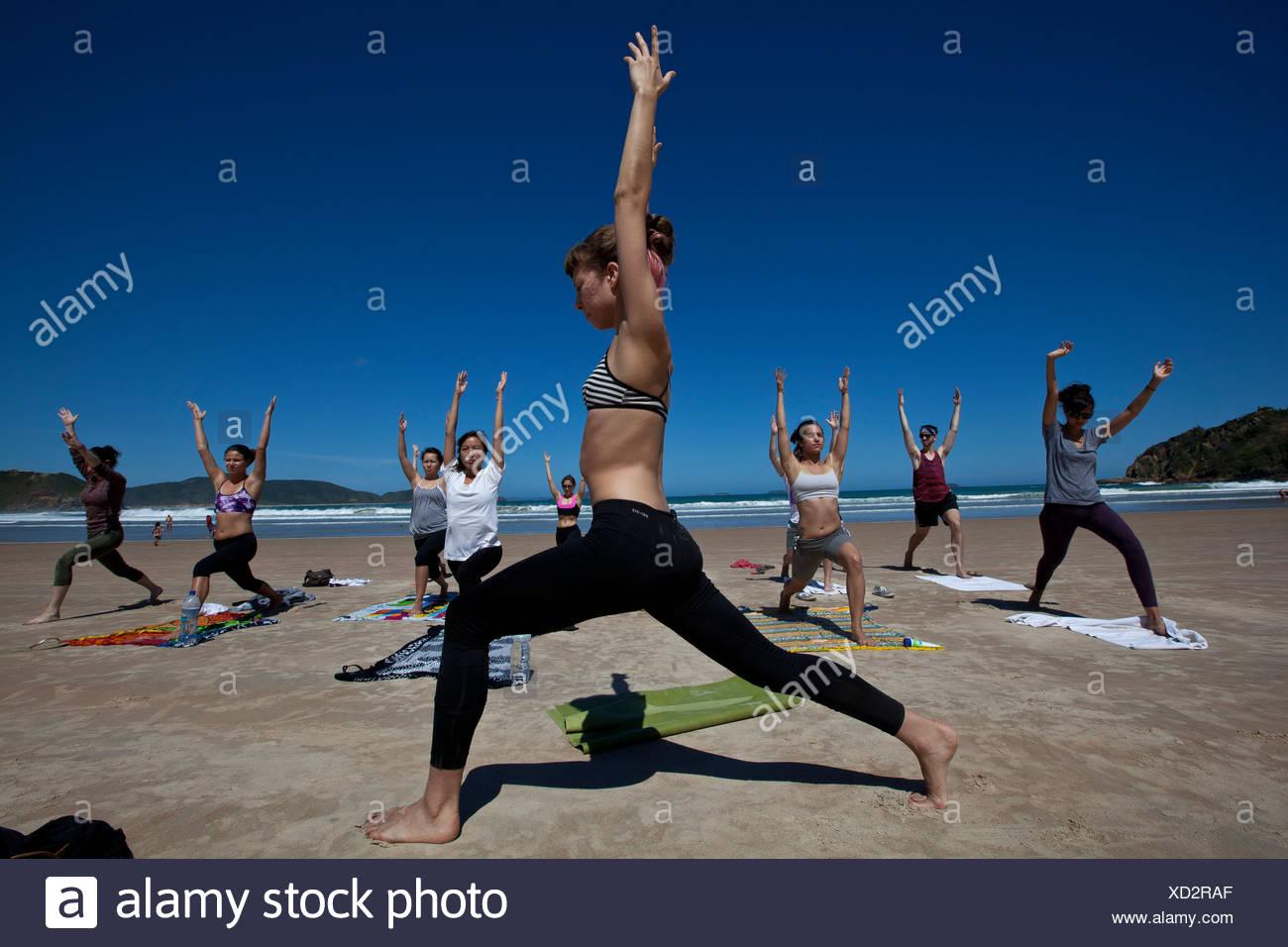 Young people practicing yoga at Geriba beach, Armacao de Buzios, Rio de  Janeiro State bb802fb3e2