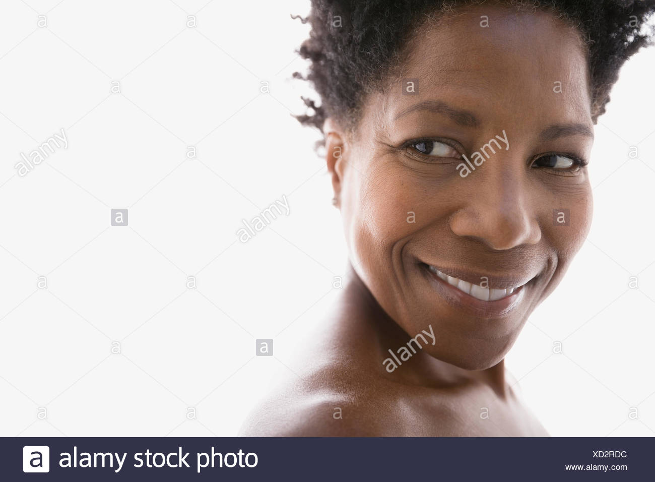 Close up of smiling woman looking over shoulder - Stock Image