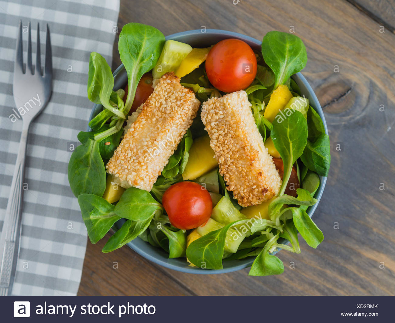 Baked feta cheese in sesame crust on mixed salad with mango Stock Photo