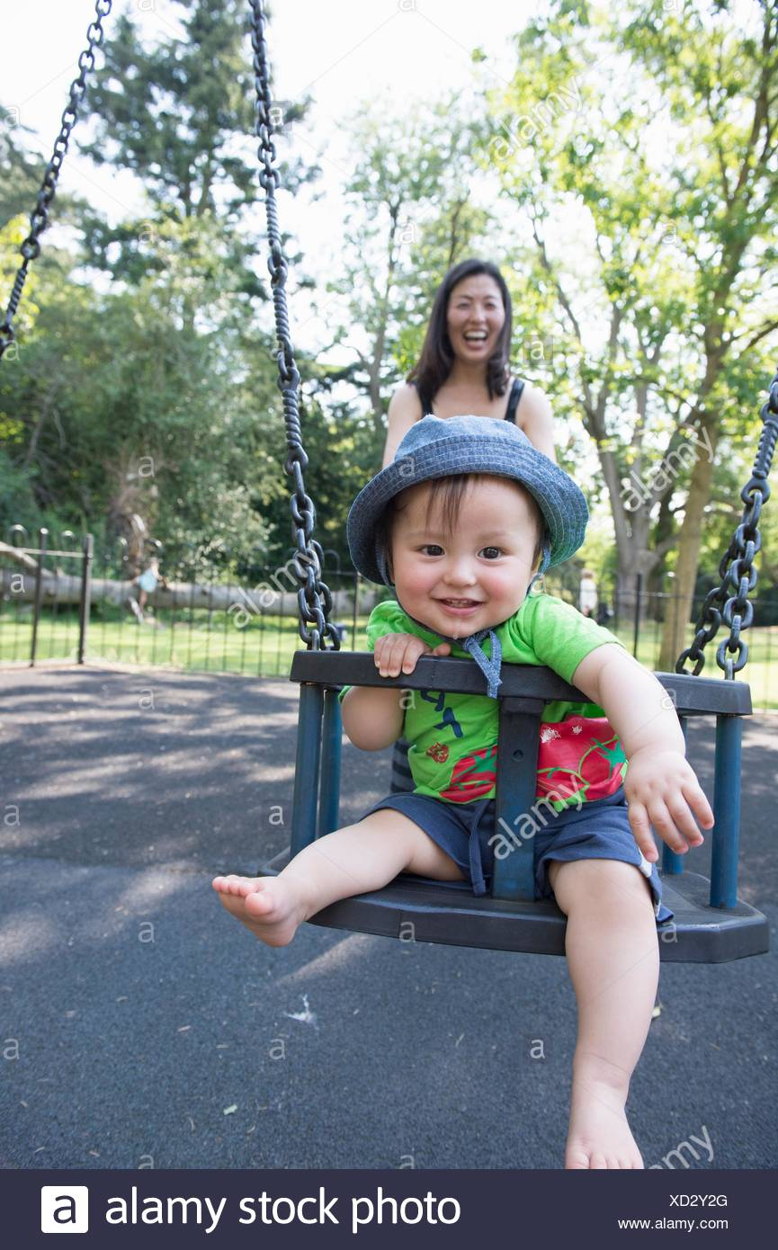 Portrait of baby boy with mother playing on park swing - Stock Image