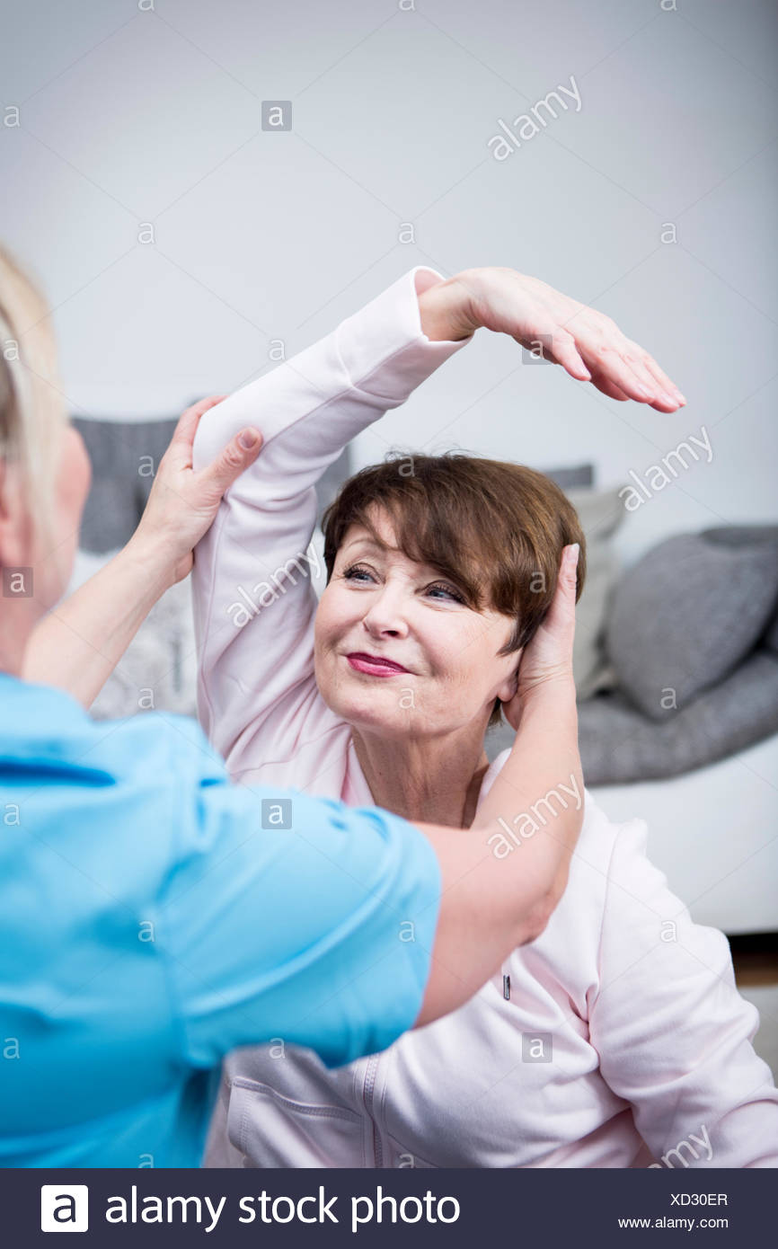 Gereatric nurse doing physio therapy with patient - Stock Image